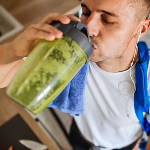 man drinking green smoothie